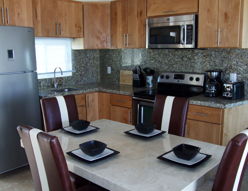 The kitchen has many new amenities such as a full oven, microwave, coffee maker, toaster, blender and everything you need to make your stay like home. Enjoy the views and TV from the marble dining set.